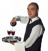 Waiter pouring glasses of wine — Stock Photo