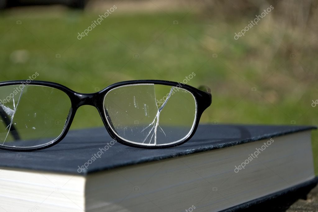 Royalty Free Stock Image of a close-up photograph of a pair of broken spectacles on top of a book. Shot under natural sunlight with plenty of copyspace. — Stock Photo #9196929