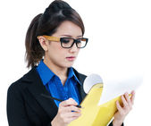 Beautiful young businesswoman looking at clipboard — Stock Photo