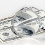Dollar bills on the magnifying glass — Stock Photo