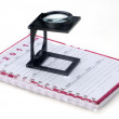 Magnifier with notepad — Stock Photo
