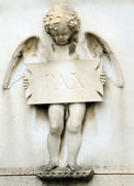 Angelic figure holding plate with inscription pax ( peace ) — Stock Photo