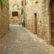 Narrow  paved street and stone walls in italian village - Stock Photo