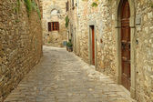Narrow paved street and stone walls in italian village — Stock Photo