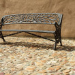 Vintage bench on paved sidewalk - Zdjcie stockowe