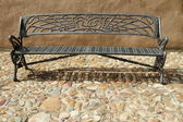 Vintage bench on paved sidewalk — Stock Photo