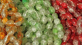 Green, red and orange glass beads background — Stock Photo