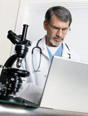 Doctor Analyzing Data at Laptop Computer and Microscope — Stock Photo