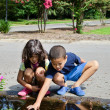 Children Watching Tadpoles In A Street Puddle - Stockfoto