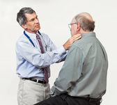 Doctor Examining Senior Patient's Swollen Glands — Stockfoto
