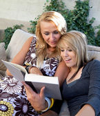 Mother and Teenage Daughter Reading Book Together — Stock Photo