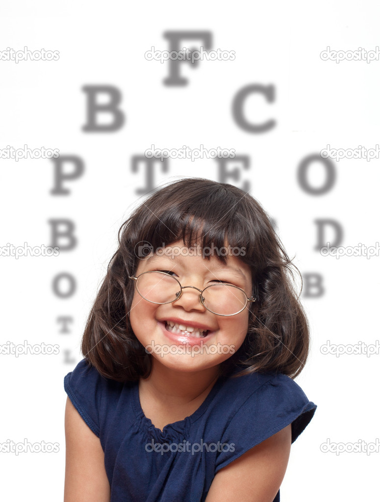 Cute little girl with glasses grinning in front of eye chart in the background. Children at the eye doctor theme. — Stock Photo #8605681