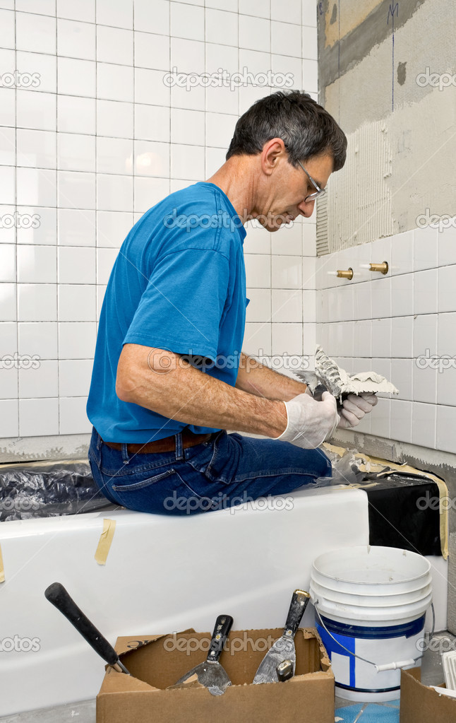 Man applying ceramic tile to a bathtub enclosure wall. — Stock Photo #9671775