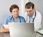 Doctor and Nurse Reviewing on Laptop Computer in Office — Stock Photo