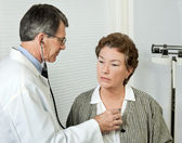 Doctor Listens to Patient's Heart — Stock Photo