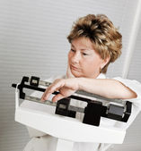 Mature Woman on Weight Scale — ストック写真