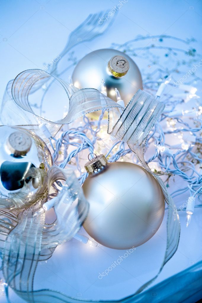 An abstract tangle of glowing silvery Christmas ornaments with translucent ribbons, sparkling gold stars and twinkling white lights. Short depth of field with glowing effects and toned blue.  Stock Photo #9698885