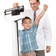 Doctor Weighing Cheering Little Boy on Weight Scale — Stock Photo