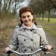 Happy woman riding a bicycle - Stock Photo
