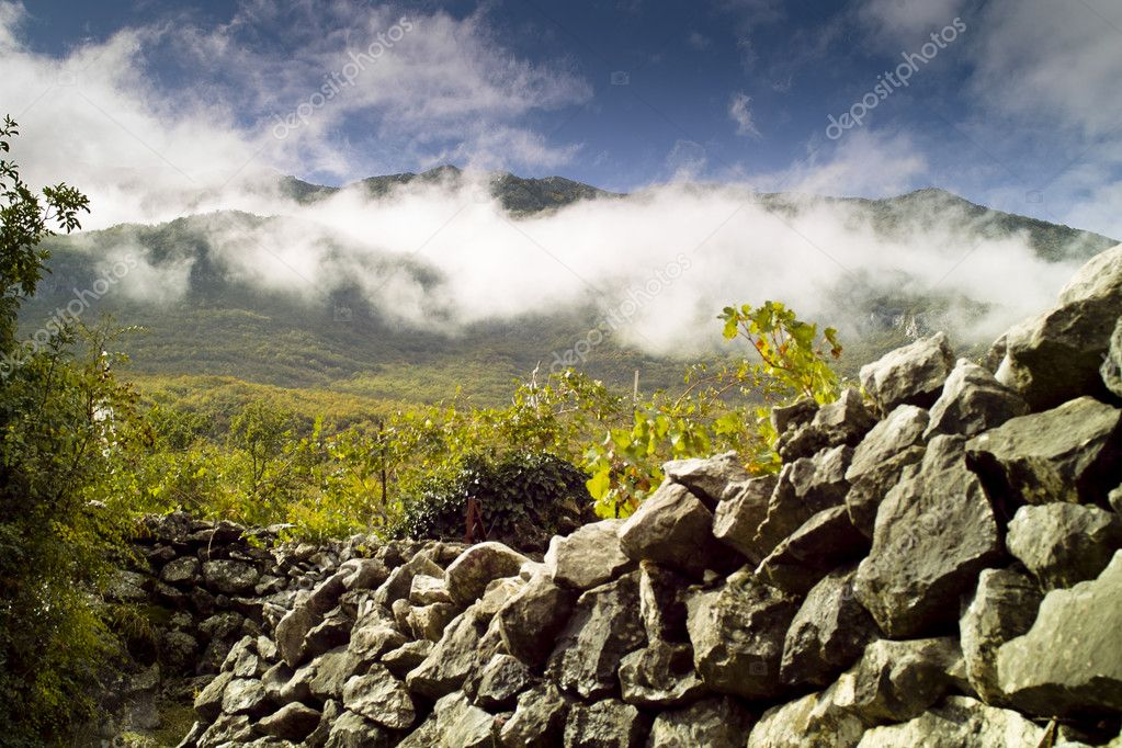 Mountain summit in fog and ancient stone wall — Stock Photo #8421442