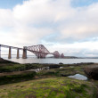 Stock Photo: Forth Rail Bridge with foreground rocks in Scotland