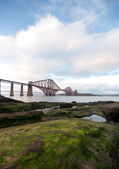 Forth Rail Bridge with foreground rocks in Scotland — Stock Photo