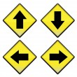 Group of four yellow road signs with arrows - Stock Photo