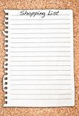 Cork arka plan üzerinde dikey alışveriş listesi — Stok fotoğraf