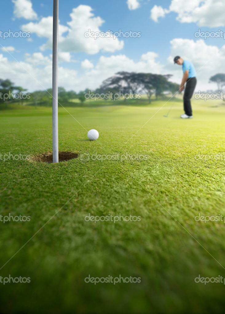Golfer putting at golf course, shallow depth of field  Stock Photo #8990501
