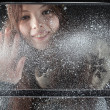 Young happy girl behind snow window — Stock Photo