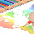 Stock Photo: Color pencils and world map