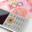 Mobile phone and chinese currency — Stock Photo