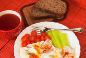 Fried egg with cup of tea — Stock Photo