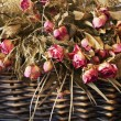Arrangement of dried roses in a basket — Stock Photo #8580501