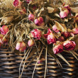 Stock Photo: Arrangement of dried roses in a basket