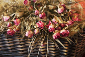 Arrangement of dried roses in a basket — Stock Photo