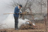 Man burn out dry grass in the garden — Stock Photo