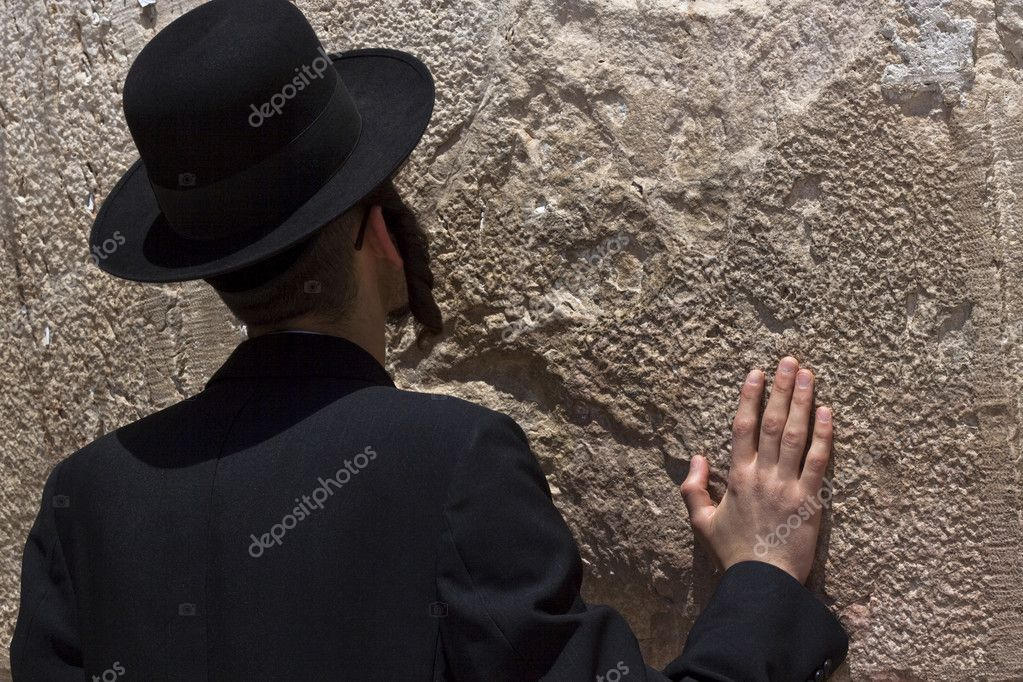 Jewish religious man praying at the western wall with one hand on the wall — Stock Photo #8385524