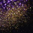 Gold and purple glitter on black background — Stock Photo