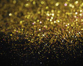 Gold glitter on black background — Stock Photo