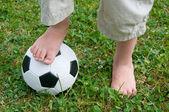 Pies de niños en un balón de fútbol — Stockfoto