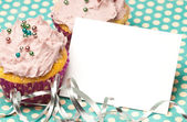 Cupcakes with a blank invitation — Stock Photo