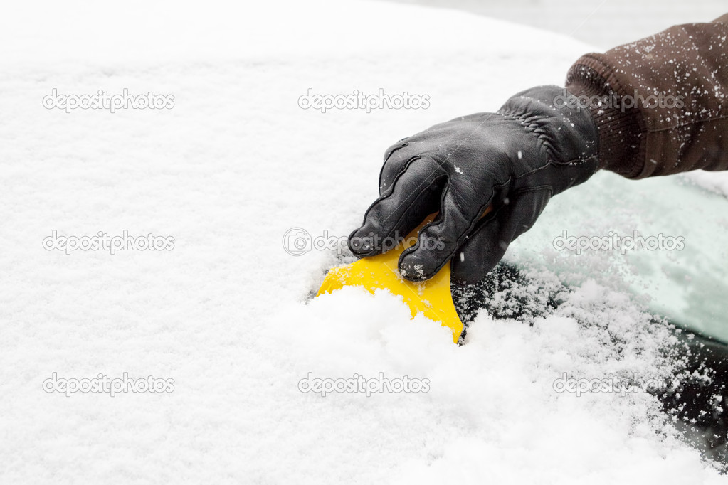 Scraping snow and ice from the car windscreen  Stock Photo #9139678