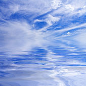 Sunlit clouds over water — Stock Photo