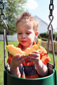 Boy eating melon — Stock Photo