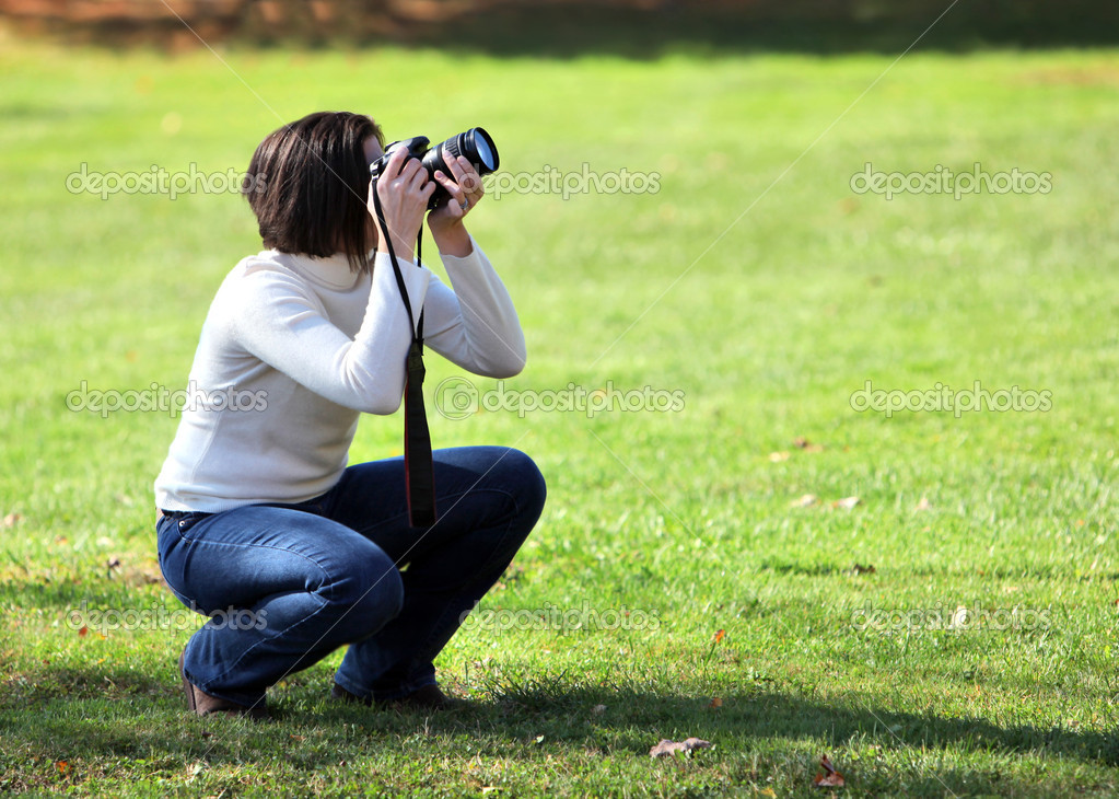 Pretty woman crouching with camera outdoors — Stock Photo #8408662