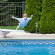 Stock Photo: Boy jumping into pool