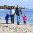 Family of four at the beach — Stock Photo