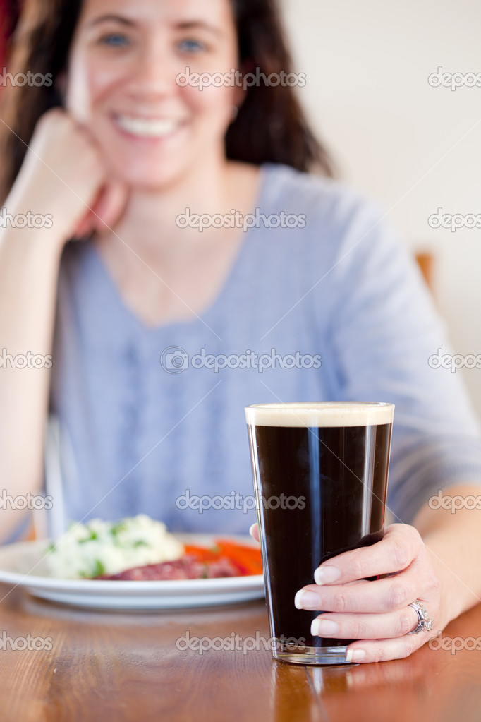 Young woman holding a pint with lunch at a pub  Stock Photo #8866529