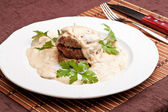 Roasted meat under white sauce — Stock Photo